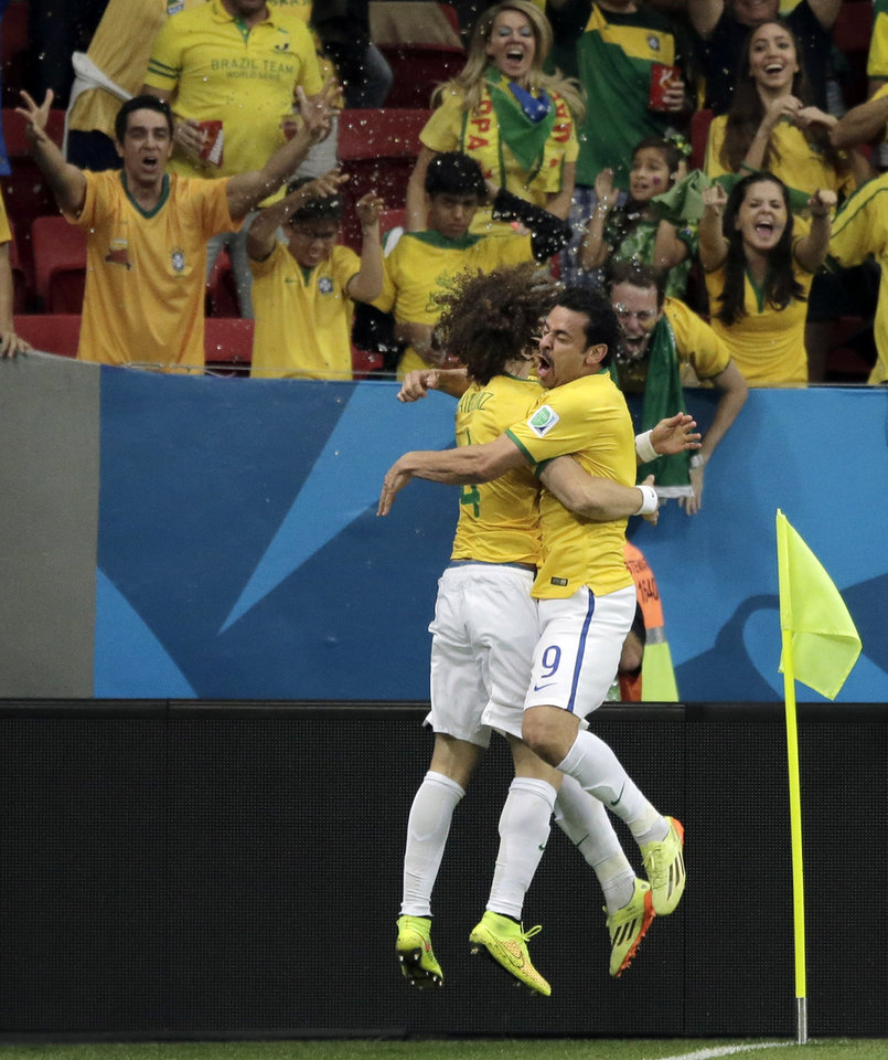 Photo - Brazil's Fred, right, celebrates with Brazil's David Luiz after scoring his side's third goal during the group A World Cup soccer match between Cameroon and Brazil at the Estadio Nacional in Brasilia, Brazil, Monday, June 23, 2014. (AP Photo/Bernat Armangue)