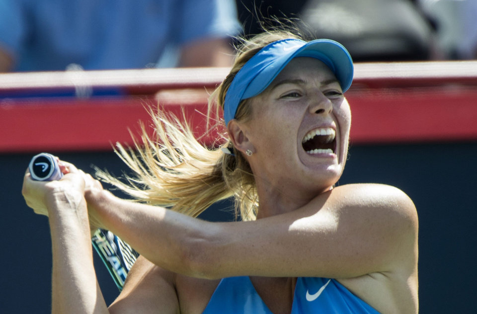Photo - Maria Sharapova of Russia yells as she returns to Garbine Muguruza of Spain at the Rogers Cup tennis tournament Wednesday Aug. 6, 2014 in Montreal. (AP Photo/The Canadian Press, Paul Chiasson)