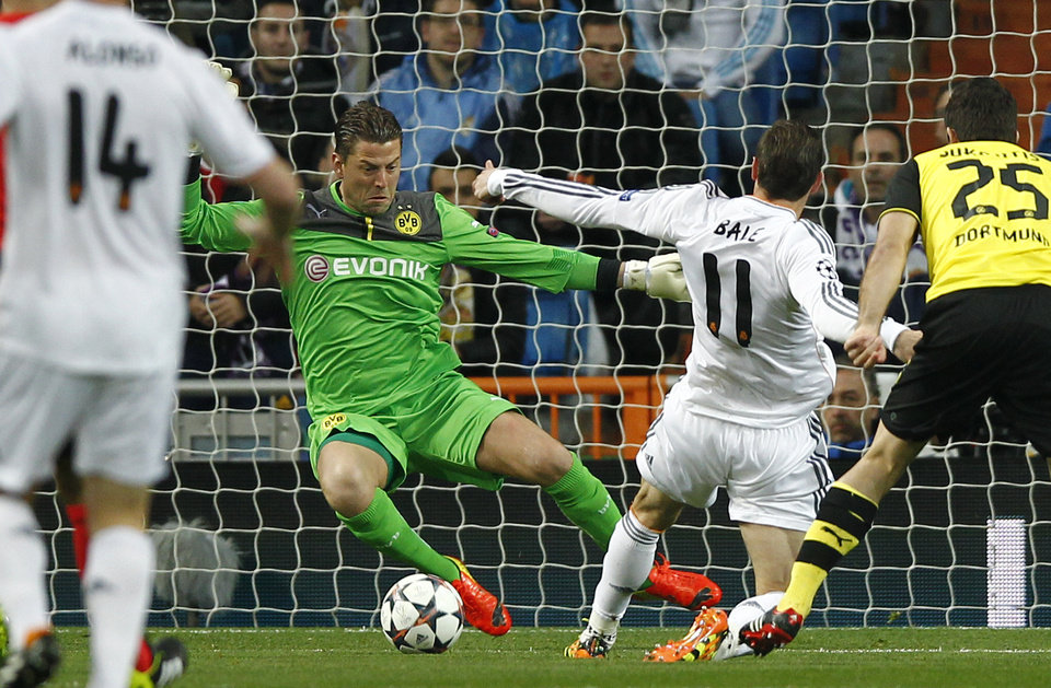 Photo - Real's Gareth Bale, second right, scores the opening goal past Dortmund goalkeeper Roman Weidenfeller during a Champions League quarterfinal first leg soccer match between Real Madrid and Borussia Dortmund at the Santiago Bernabeu   stadium in Madrid, Spain, Wednesday, April 2, 2014. (AP Photo/Andres Kudacki)