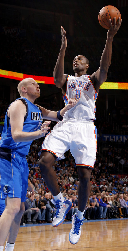 Oklahoma City\'s Serge Ibaka (9) goes to the basket past Dallas\' Chris Kaman (35) during an NBA basketball game between the Oklahoma City Thunder and the Dallas Mavericks at Chesapeake Energy Arena in Oklahoma City, Thursday, Dec. 27, 2012. Photo by Bryan Terry, The Oklahoman
