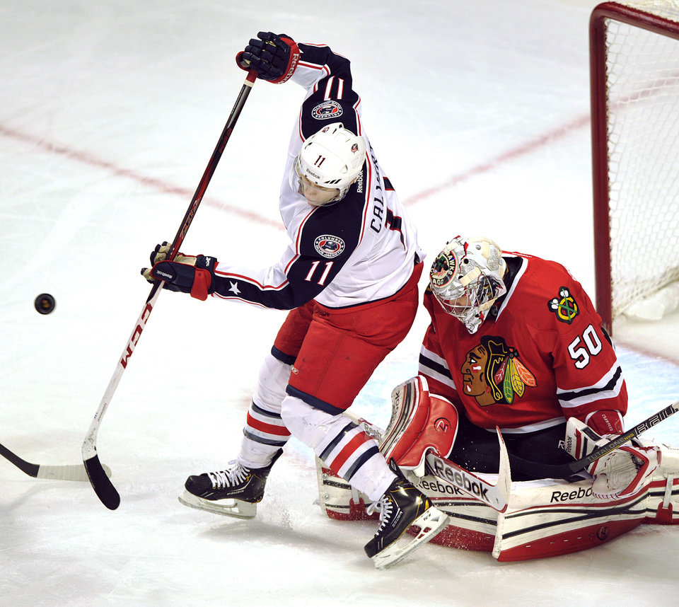 Photo - Columbus Blue Jackets' Matt Calvert (11) tries to tip the puck past Chicago Blackhawks goalie Corey Crawford (50) during the first period of an NHL hockey game Sunday, Feb. 24, 2013, in Chicago. (AP Photo/Jim Prisching)