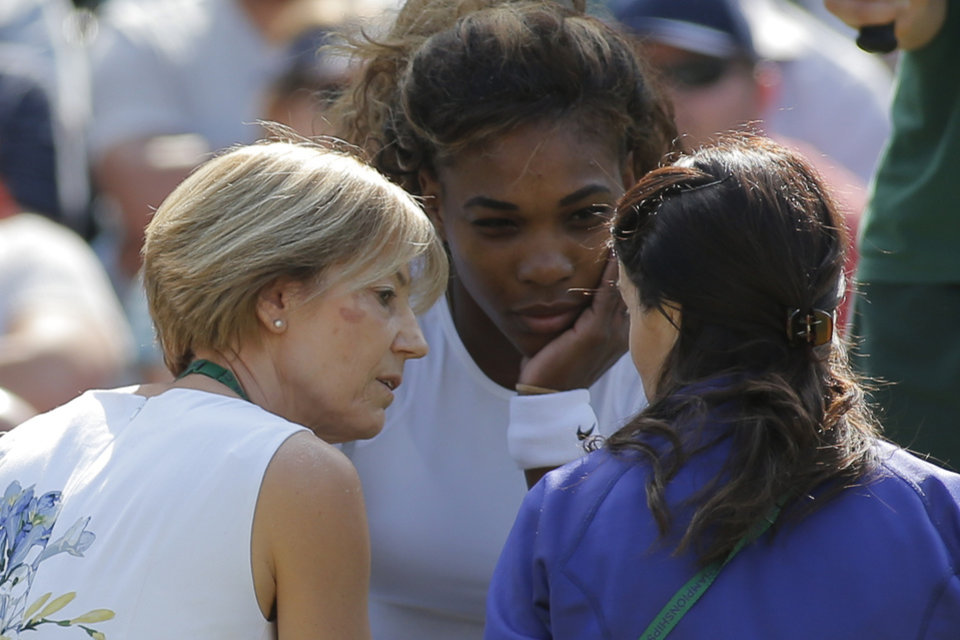 Photo - Court officials talk to Serena Williams of the U.S as she and Venus Williams retire after 3 games from their women's doubles match against Kristina Barrois of Germany and Stefanie Voegele of Switzerland at the All England Lawn Tennis Championships in Wimbledon, London, Tuesday July 1, 2014. (AP Photo/Pavel Golovkin)