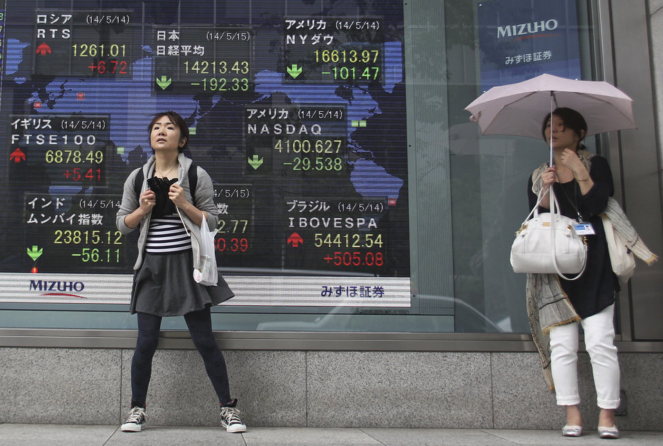Photo - People take shelter from rain under an awning of securities' firm in Tokyo, Thursday, May 15, 2014.  Asian stocks mostly drifted lower Thursday as robust growth in Japan was offset by U.S. markets pulling back from record levels. Tokyo's Nikkei 225 stock index fell 0.9 percent to 14,279.69 despite the government reporting that the economy expanded at an annualized 5.9 percent in the first quarter, the fastest pace in nearly three years. (AP Photo/Junji Kurokawa)