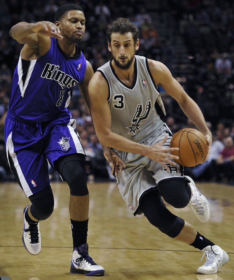 Photo - San Antonio Spurs guard Marco Belinelli, right, drives around Sacramento Kings forward Rudy Gay during the first half of an NBA basketball game, Saturday, Feb. 1, 2014, in San Antonio. (AP Photo/Darren Abate)