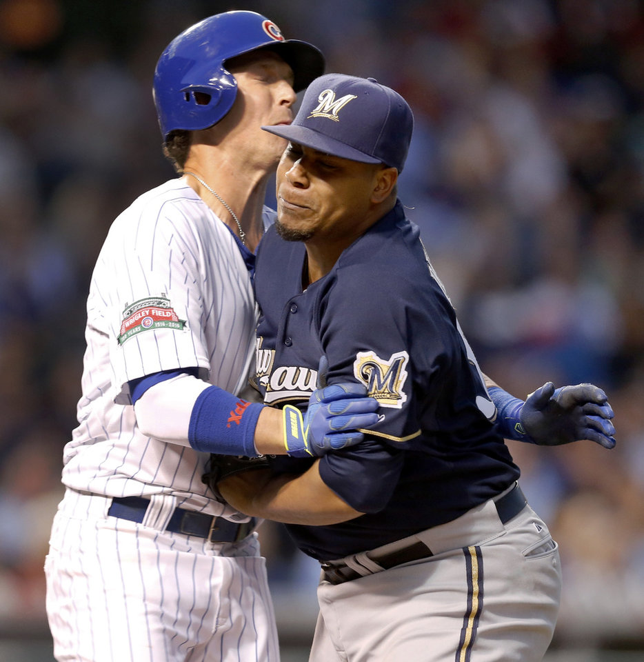Photo - Chicago Cubs' Chris Coghlan, left, collides with Milwaukee Brewers starting pitcher Wily Peralta as Peralta tags Coghlan out on the first baseline during the third inning of a baseball game Tuesday, Aug. 12, 2014, in Chicago. (AP Photo/Charles Rex Arbogast)