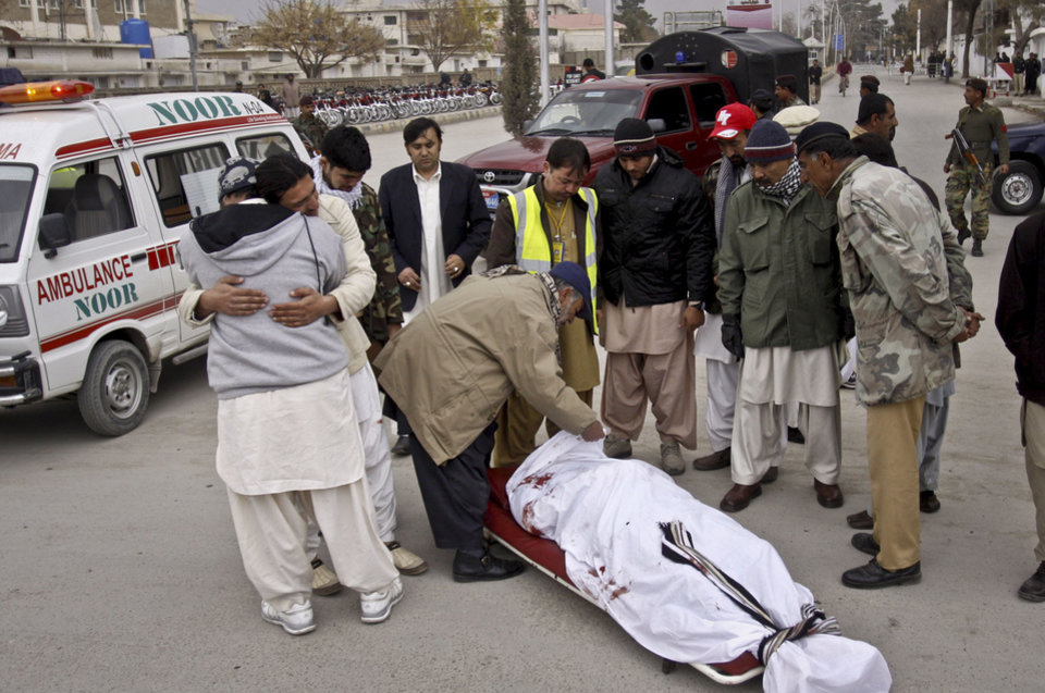 Photo - People look at the lifeless body of a government official killed in Quetta, Pakistan, Monday, Dec. 17, 2012. Gunmen killed a provincial government spokesman in the southwest Pakistan in an apparent sectarian attack, and then shot to death two nearby policemen, police said. (AP Photo/Arshad Butt)