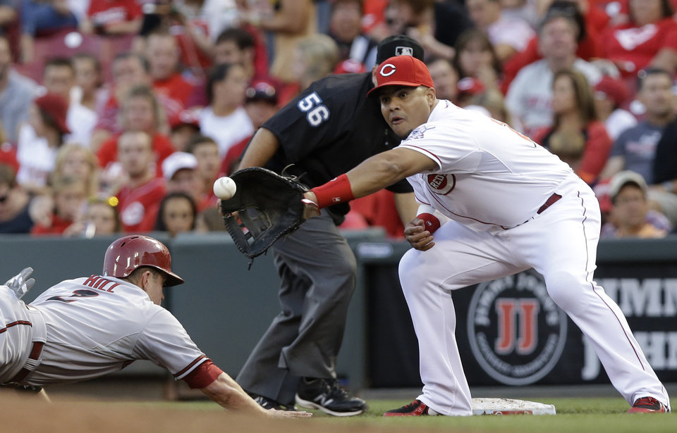 Photo - Arizona Diamondbacks' Aaron Hill (2) dives safely back to first base as Cincinnati Reds first baseman Brayan Pena catches a pickoff throw from starting pitcher Mike Leake in the fourth inning of a baseball game, Tuesday, July 29, 2014, in Cincinnati. (AP Photo/Al Behrman)