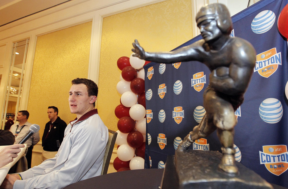 CORRECTS YEAR - Texas A&M freshman quarterback Johnny Manziel answer questions during a Cotton Bowl press conference, with a Heisman Trophy at side, at the Omni Mandalay hotel, Tuesday, Jan. 1, 2013, in Irving, Texas. Texas A&M plays Oklahoma on Jan. 4 in the Cotton Bowl in Arlington, Texas. (AP Photo/Brandon Wade) ORG XMIT: TXBW103