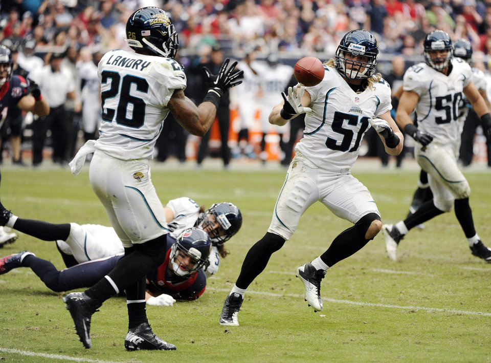 Photo -   Jacksonville Jaguars' Paul Posluszny (51) tosses the ball to Dawan Landry (26) after intercepting a pass from the Houston Texans during the fourth quarter of an NFL football game, Sunday, Nov. 18, 2012, in Houston. (AP Photo/Dave Einsel)