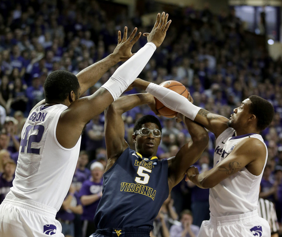 Photo - West Virginia's Devin Williams (5) looks to pass the ball under pressure from Kansas State's Thomas Gipson (42) and Shane Southwell during the first half of an NCAA college basketball game Saturday, Jan. 18, 2014, in Manhattan, Kan. (AP Photo/Charlie Riedel)