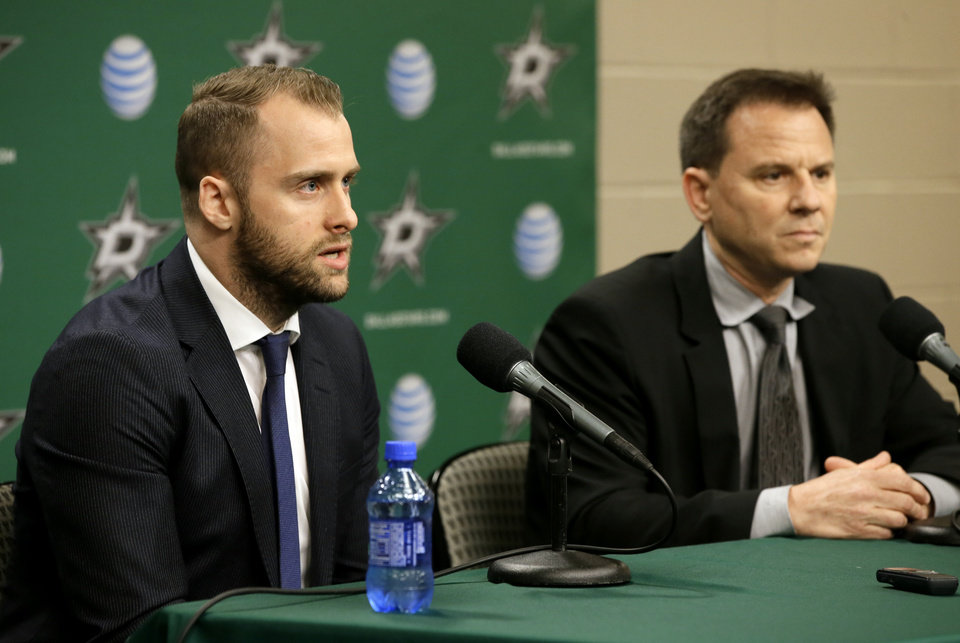 Photo - Dallas Stars center Rich Peverley, left, responds to questions during a news conference as team physician Dr. Robert Dimeff, right, watches before an NHL hockey game against the Nashville Predators, Friday, March 28, 2014, in Dallas. Peverley collapsed on the bench during a game earlier this month. He then had surgery to correct an abnormal heart rhythm. (AP Photo/Tony Gutierrez)