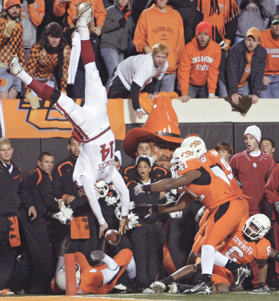 Oklahoma quarterback Sam Bradford (14) is flipped upside down as he leaps over Oklahoma State's Orie Lemon (41) during the second half Saturday in Stillwater. PHOTO BY CHRIS LANDSBERGER