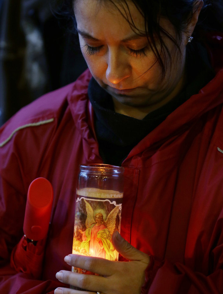 Photo - Anna Schoneker holds a guardian angel candle Tuesday, March 25, 2014, at a candlelight vigil in Arlington, Wash., for the victims of a massive mudslide that struck the nearby community of Oso, Wash., on Saturday, killing at least 16 people and leaving dozens missing. (AP Photo/Ted S. Warren)