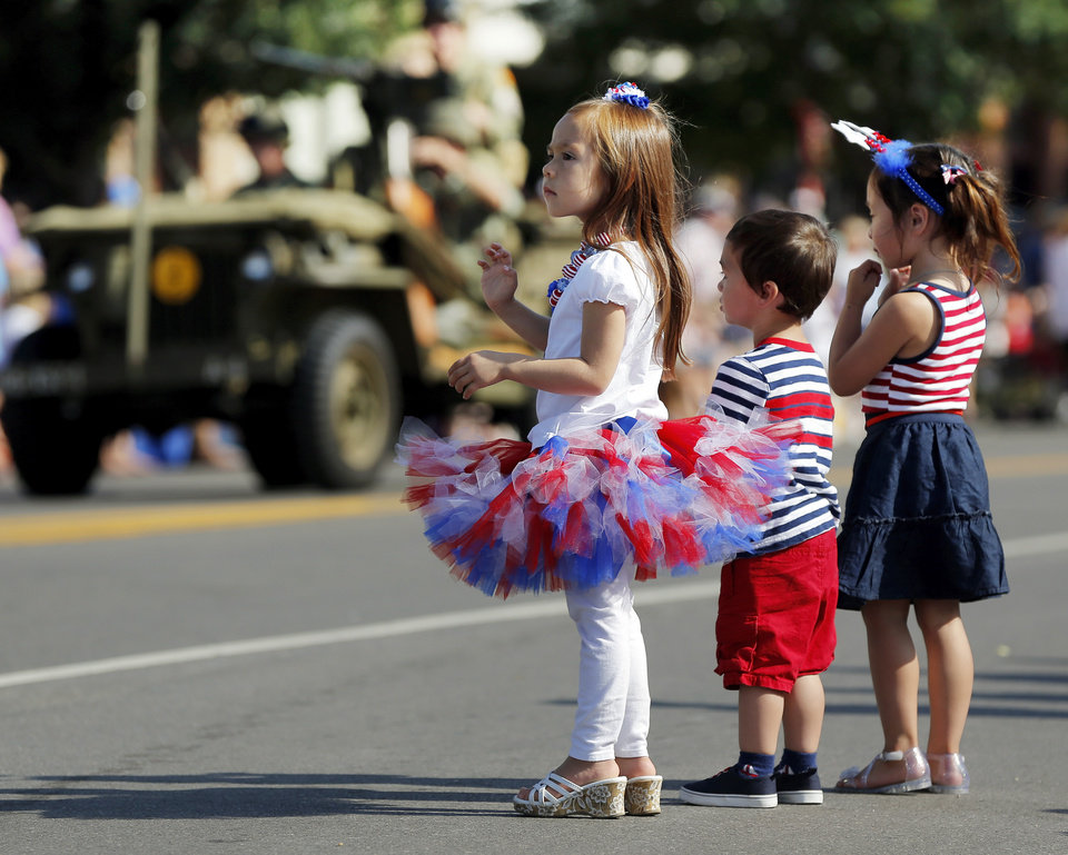 Photo - From left, Lilyannah Powers, 4, Daemon Riley, 2, and Aiyana Riley, 4, watch the Edmond LibertyFest Parade in downtown Edmond, Okla., on Independence Day, Friday, July 4, 2014. Photo by Nate Billings, The Oklahoman