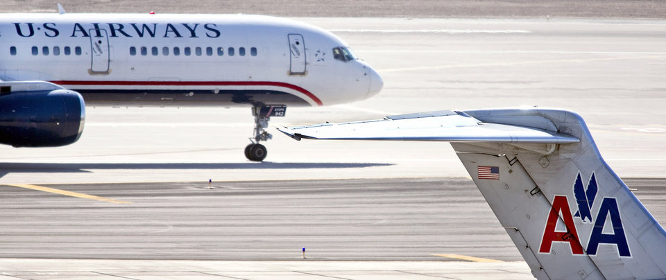Photo - FILE - In this Feb. 7, 2013 file photo, a US Airways jet taxis past an American Airlines jet parked at the gate at Sky Harbor International Airport in Phoenix. The merger of US Airways and American Airlines has given birth to a mega airline with more passengers than any other in the world. (AP Photo/The Arizona Republic,Tom Tinkle, File)  MARICOPA COUNTY OUT; MAGS OUT;