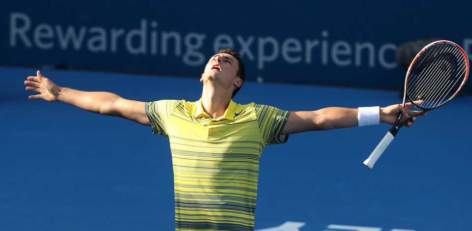 Photo - Australia's Bernard Tomic spreads out his arms after defeating Sergiy Stakhovsky of Ukraine in their men's singles semifinal match at the Sydney International tennis tournament in Sydney, Friday, Jan. 10, 2014. Tomic won the match 6-7, 7-5, 6-3. (AP Photo/Rick Rycroft)