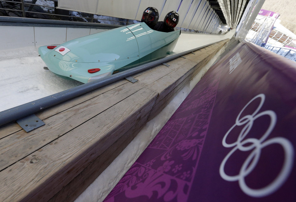 Photo - The JPN-1 team from Japan brake in the finish area after a training run for the men's two-man bobsled at the 2014 Winter Olympics, Wednesday, Feb. 5, 2014, in Krasnaya Polyana, Russia.  (AP Photo/Michael Sohn)