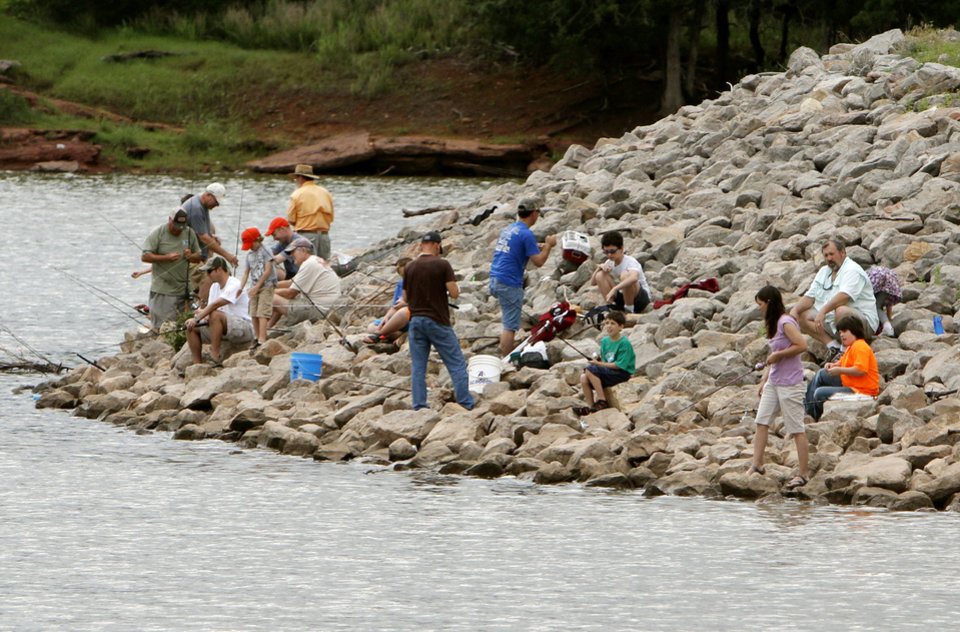 Photo -  Children and parents line the banks of Arcadia Lake for the kids fishing derby on Saturday. PHOTO BY PAUL HELLSTERN, THE OKLAHOMAN   PAUL HELLSTERN -