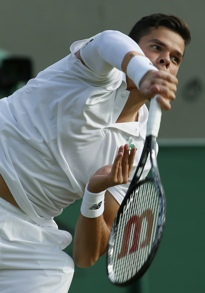 Photo - Milos Raonic of Canada serves to Lukasz Kubot of Poland during their men's singles match at the All England Lawn Tennis Championships in Wimbledon, London, Saturday, June 28, 2014. (AP Photo/Alastair Grant)