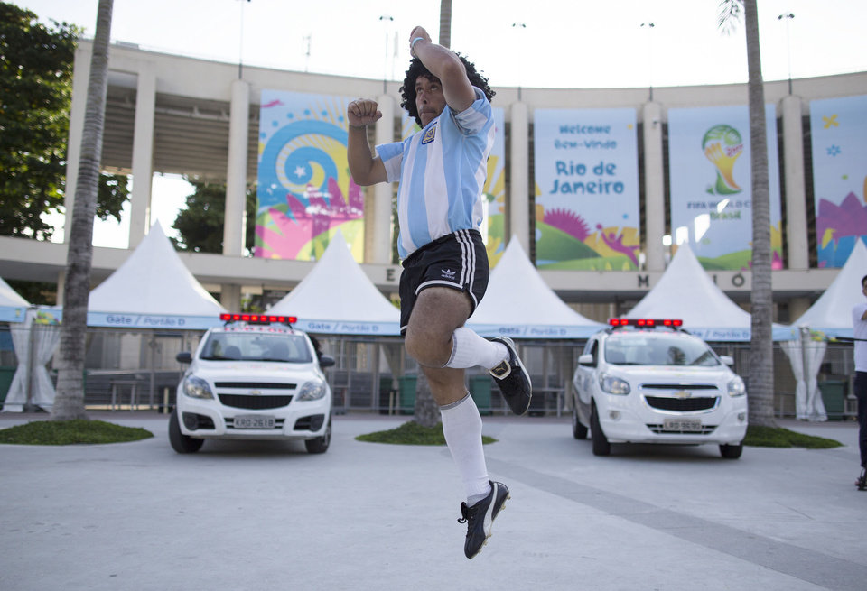Photo - Street performing mime, Daniel Gonzalez, 35, who is dressed to resemble Argentine soccer great Diego Armando Maradona, jumps during his perfromance in front of Maracana stadium, Rio de Janeiro, Brazil, Wednesday, June 11, 2014. The World Cup soccer tournament starts Thursday. (AP Photo/Leo Correa)