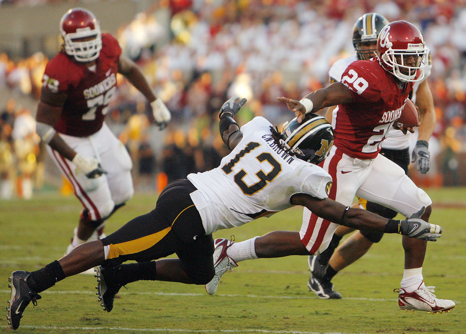 Photo - Oklahoma's Chris Brown (29) tries to get  past Missouri's Cornelius Brown (13) with a stiff arm during the first half of the college football game between  the University of Oklahoma Sooners (OU) and the University of Missouri Tigers (MU) at the Gaylord Family Oklahoma Memorial Stadium on Saturday, Oct. 13, 2007, in Norman, Okla.By CHRIS LANDSBERGER, The Oklahoman