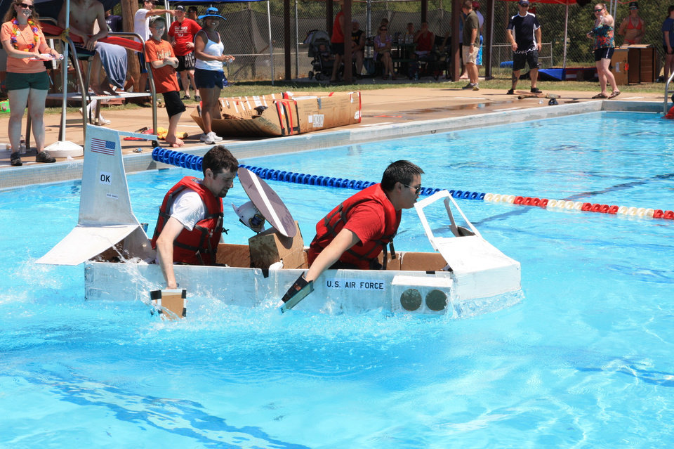 "Wind blows off the radar dome hat from Matthew Maupin, left, as he and Sanford Ang paddle their ""AWACS in a Box"" cardboard boat across the Tinker Air Force Base pool Saturday afternoon.  Photo by Thomas Maupin"