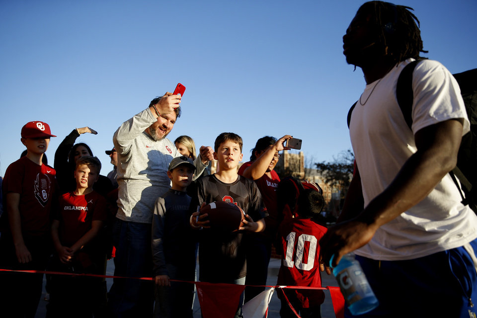 Photo - Fans watch the Oklahoma team arrive before an NCAA football game between the University of Oklahoma Sooners (OU) and the Iowa State University Cyclones at Gaylord Family-Oklahoma Memorial Stadium in Norman, Okla., Saturday, Nov. 9, 2019. [Bryan Terry/The Oklahoman]