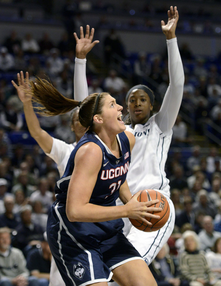 Photo - Connecticut's Stefanie Dolson (31) drives to the basket past Penn State's Candice Agee (1) during the first half of an NCAA college basketball game, Sunday, Nov. 17, 2013, in State College, Pa. (AP Photo/John Beale)
