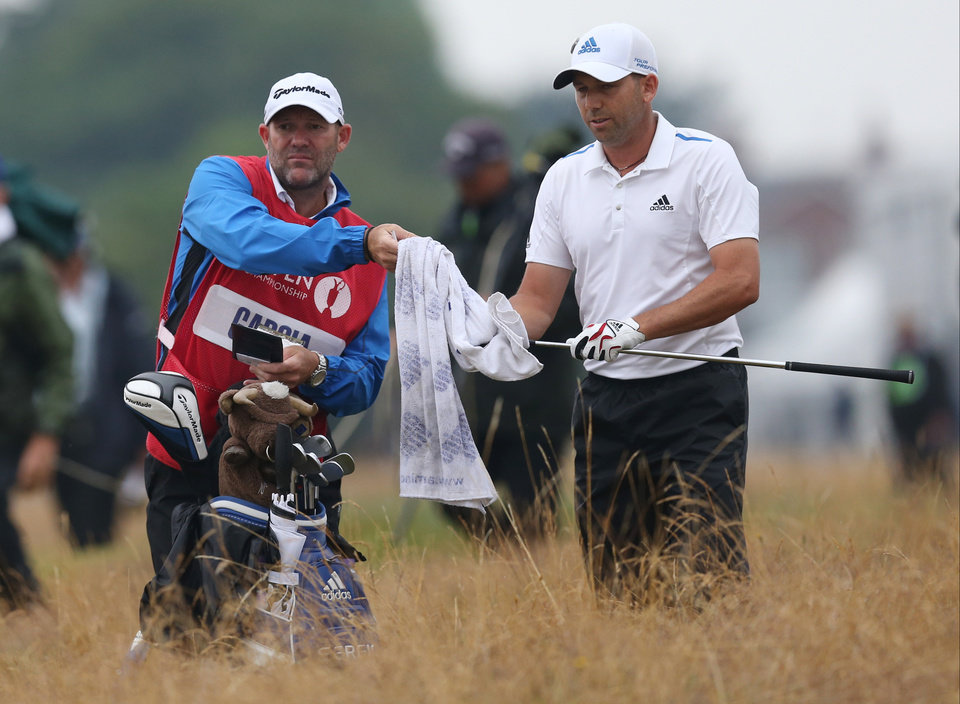 Photo - Sergio Garcia of Spain is given a towel by his caddie Neil Wallace to wipe his club prior to playing his shot from the rough on the 1st hole during the third day of the British Open Golf championship at the Royal Liverpool golf club, Hoylake, England, Saturday July 19, 2014. (AP Photo/Scott Heppell)
