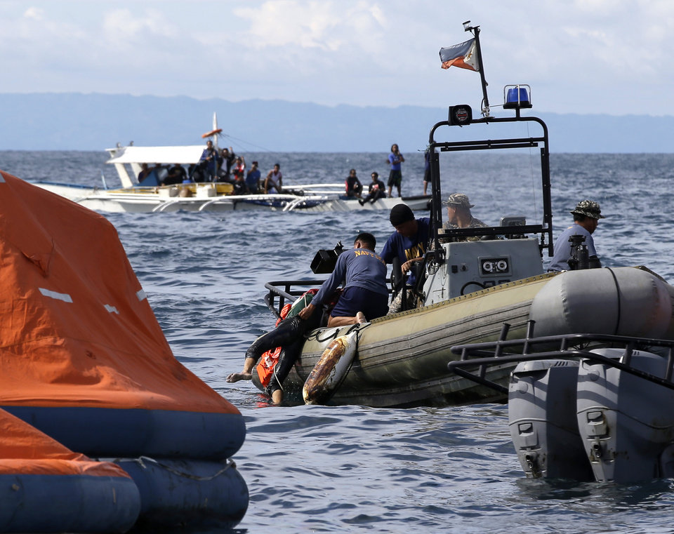 Photo - Philippine Navy divers retrieve a body from the waters off the coast of Talisay city, Cebu province, in central Philippines Saturday Aug. 17, 2013, a day after a passenger ferry MV Thomas of Aquinas collided with a cargo ship Sulpicio Express Siete. Divers combed through a sunken ferry Saturday to retrieve the bodies of more than 200 people still missing from an overnight collision with a cargo vessel near the central Philippine port of Cebu that sent passengers jumping into the ocean and leaving many others trapped. At least 28 were confirmed dead and hundreds rescued. The captain of the ferry MV Thomas Aquinas, which was approaching the port late Friday, ordered the ship abandoned when it began listing and then sank just minutes after collision with the MV Sulpicio Express, coast guard deputy chief Rear Adm. Luis Tuason said. (AP Photo/Bullit Marquez)
