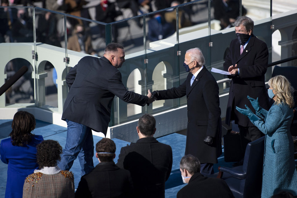 Photo - Country singer Garth Brooks shakes hands with President Joe Biden after singing at the inauguration, Wednesday, Jan. 20, 2021, at the U.S. Capitol in Washington. (Caroline Brehman/Pool Photo via AP)