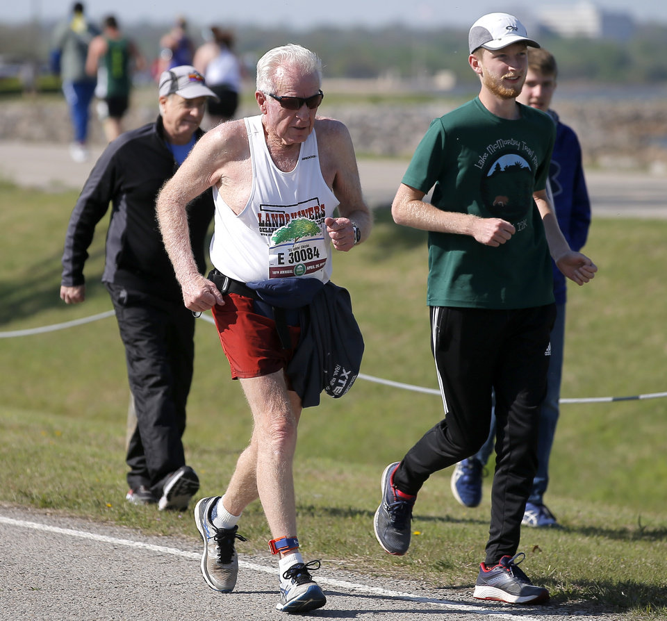 Photo - Runner Adrian Wolford is accompanied by his grandson Hayden Wolford, 17, for a short stretch around Lake Hefner during the Oklahoma City Memorial Marathon in Oklahoma City, Sunday, April 29, 2018. Photo by Bryan Terry, The Oklahoman