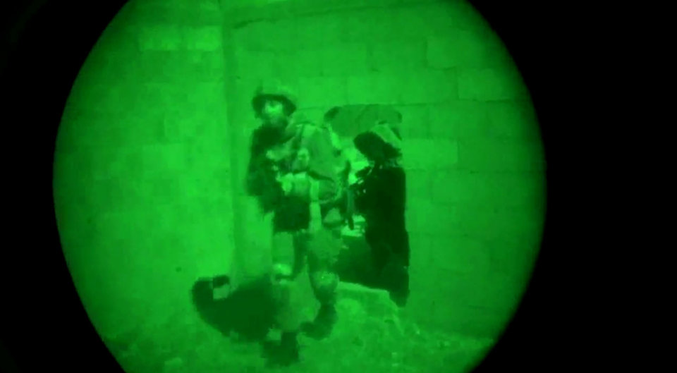 Photo - This image made from video shot through a night vision scope released by the Israeli military on Friday, July 18, 2014 shows troops moving through the opening in a wall during the early hours of a ground offensive in the Gaza Strip. Israeli troops pushed deeper into Gaza on Friday to destroy rocket launching sites and tunnels, firing volleys of tank shells and clashing with Palestinian fighters in a high-stakes ground offensive meant to weaken the enclave's Hamas rulers. (AP Photo/Israeli Defense Forces)