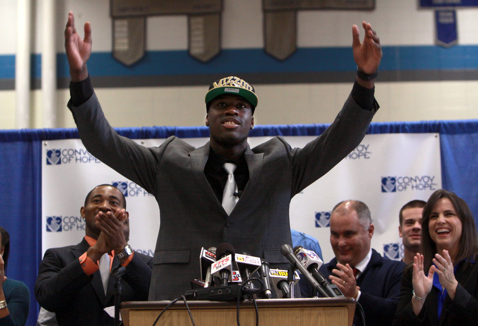 Photo - Dorial Green-Beckham, center, celebrates after announcing that he will play college football for Missouri at a press conference in Springfield, Mo., Wednesday, Feb.  1, 2012. Green-Beckham, a senior wide receiver at Hillcrest High School, was widely considered one of the top recruits in the nation. (AP Photo/Mark Schiefelbein)