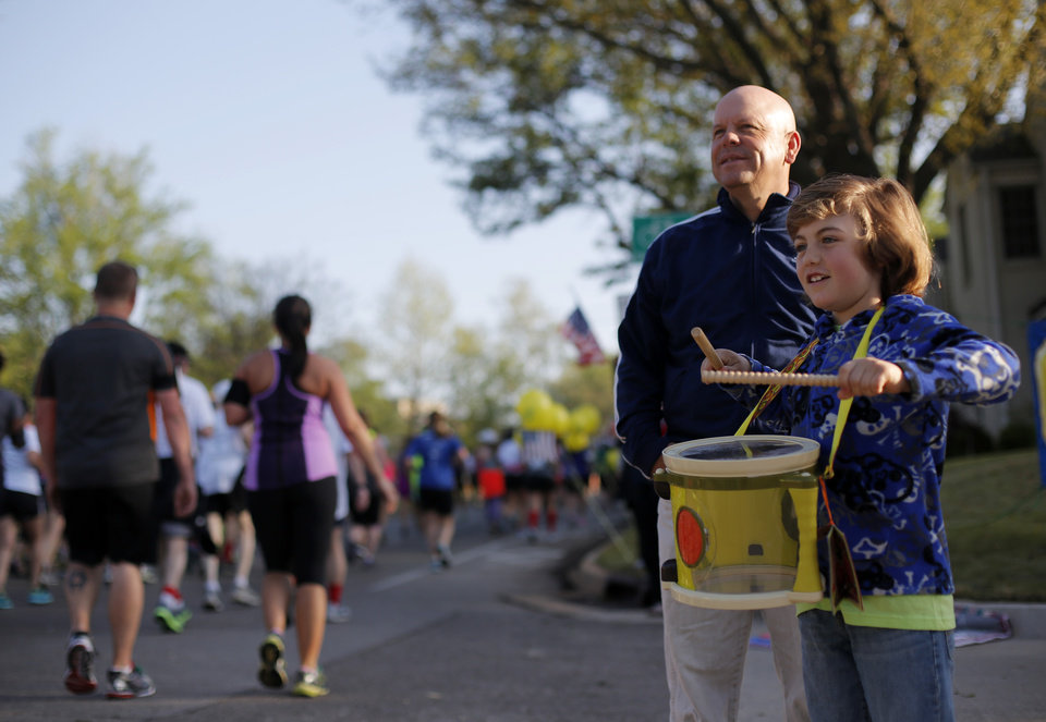Photo - Craig Starke and his son, Wyatt, 8, watch runners in the neighborhood at NE 39th and Shartel during the Oklahoma City Memorial Marathon in Oklahoma City, Sunday, April 28, 2013.  Photo by Garett Fisbeck, For The Oklahoman
