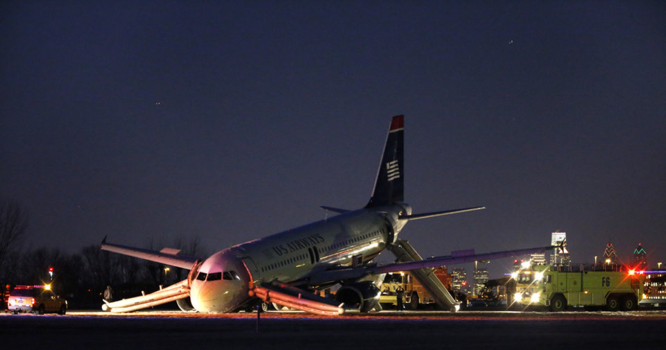 Photo - A damaged US Airways jet lies at the end of a runway at the Philadelphia International Airport, Thursday, March 13, 2014, in Philadelphia. Airline officials said the flight was heading to Fort Lauderdale, Fla., when the pilot was forced to abort takeoff around 6:30 p.m., after the front landing gear failed. An airport spokeswoman said no injuries have been reported. (AP Photo/Matt Slocum)