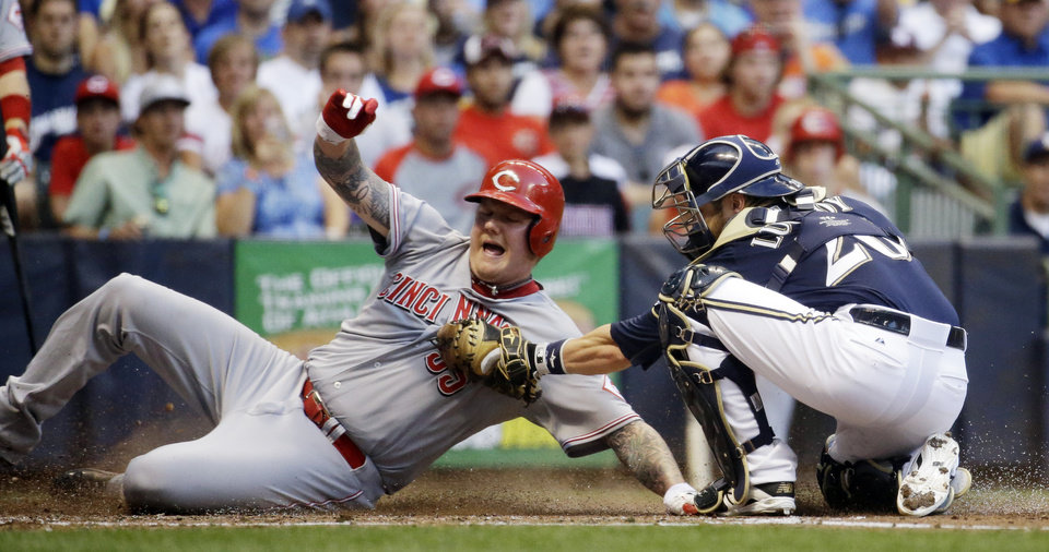 Photo - Milwaukee Brewers catcher Jonathan Lucroy tags out Cincinnati Reds' Mat Latos at home during the third inning of a baseball game Monday, July 21, 2014, in Milwaukee. Latos tried to score from third a a ball hit by Skip Schumaker. (AP Photo/Morry Gash)