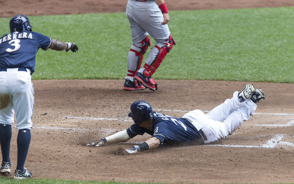 Photo - Milwaukee Brewers' Carlos Gomez slides safely home as teammate Elian Herrera gives him the down sign against the St. Louis Cardinals' during the fourth inning of a baseball game Sunday, July 13, 2014, in Milwaukee. (AP Photo/Tom Lynn)