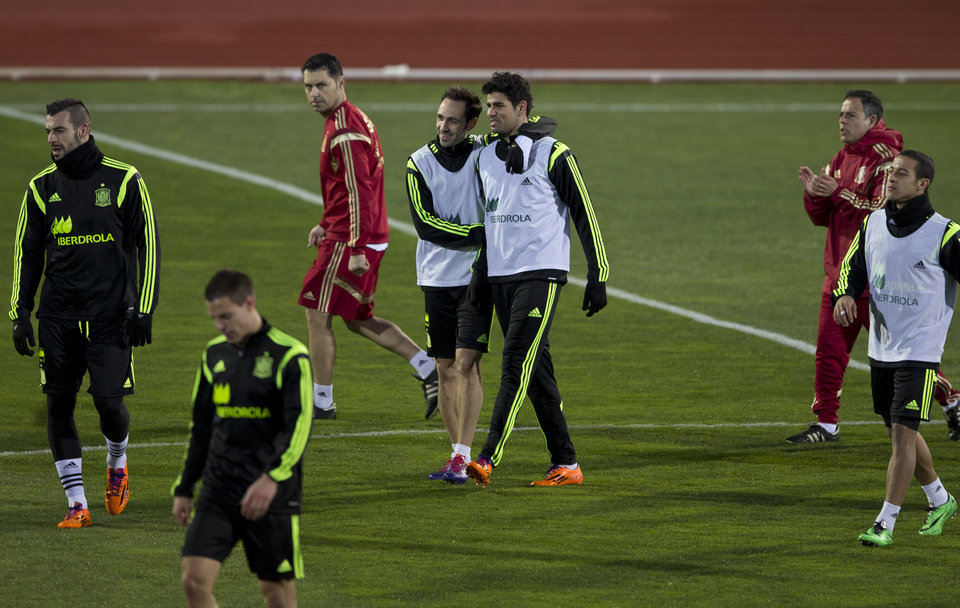 Photo - Spain's Diego Costa, centre right is hugged by Juanfran Torres during a training session in Madrid, Monday March 3, 2014. Spain will play Italy Wednesday in a friendly soccer match. (AP Photo/Paul White)