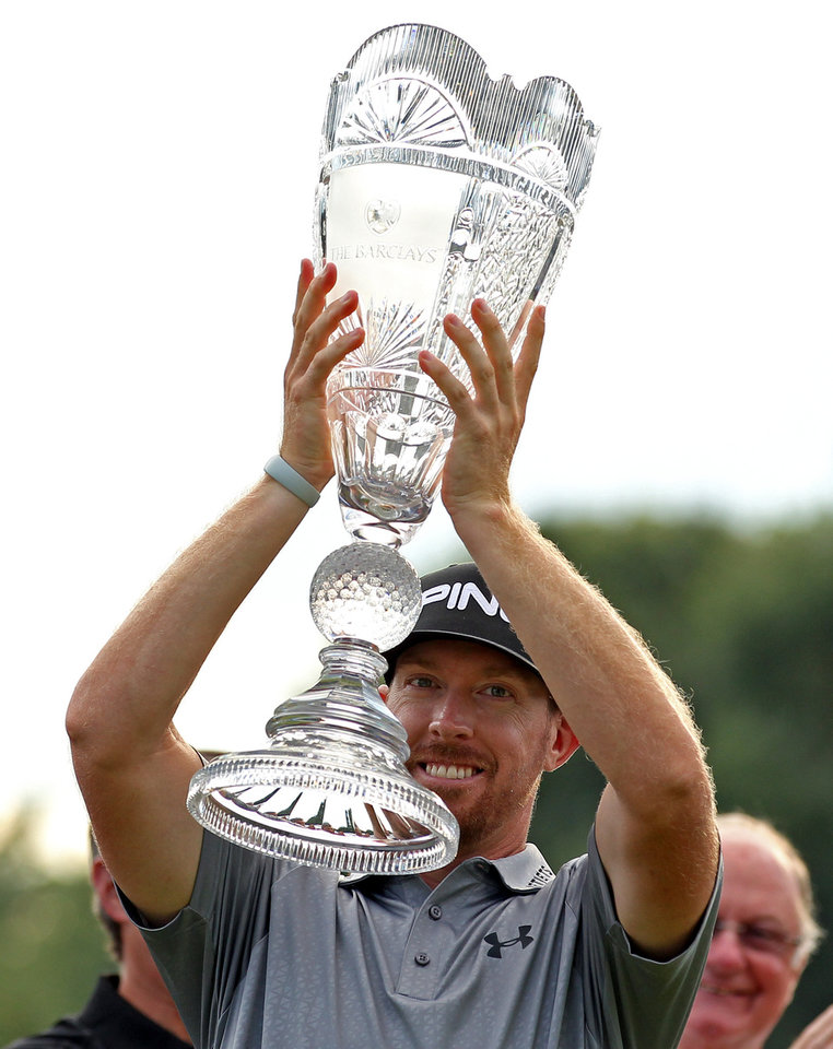 Photo - Hunter Mahan holds up the trophy after winning at The Barclays golf tournament Sunday, Aug. 24, 2014, in Paramus, N.J. Mahan won the tournament with a 14 under-par 270. (AP Photo/Adam Hunger)