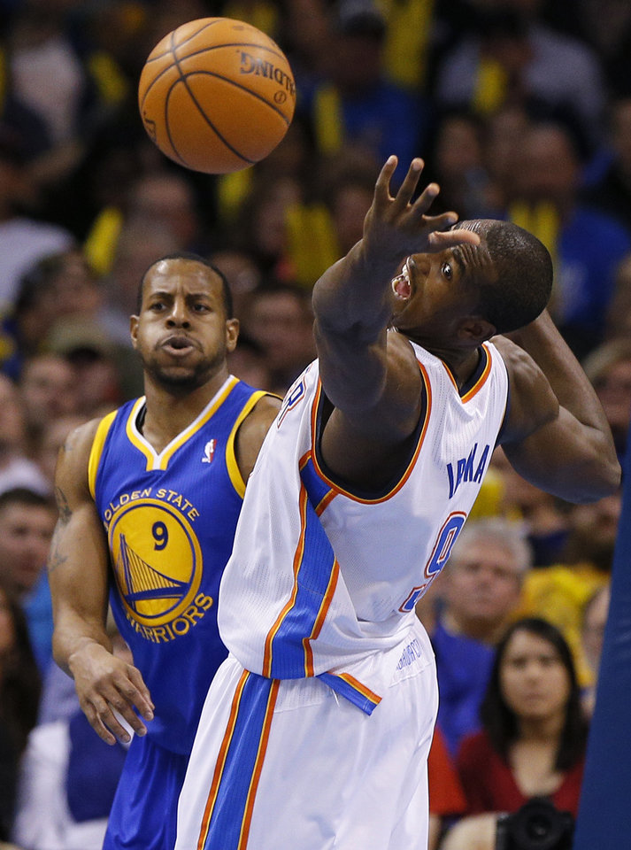 Photo - Oklahoma City's Serge Ibaka (9) reaches for the ball in front of Golden State's Andre Iguodala (9) during an NBA basketball game between the Oklahoma City Thunder and the Golden State Warriors at Chesapeake Energy Arena in Oklahoma City, Friday, Jan. 17, 2014. Photo by Bryan Terry, The Oklahoman