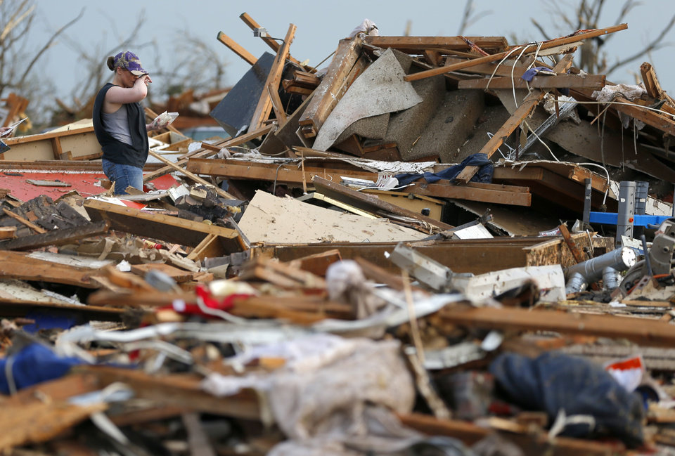 Rachel Rohweder looks through debris at a home in a residential area just west of Telephone Road in Moore, Okla., after a tornado moved through the area on Monday, May 20, 2013. Photo by Bryan Terry, The Oklahoman