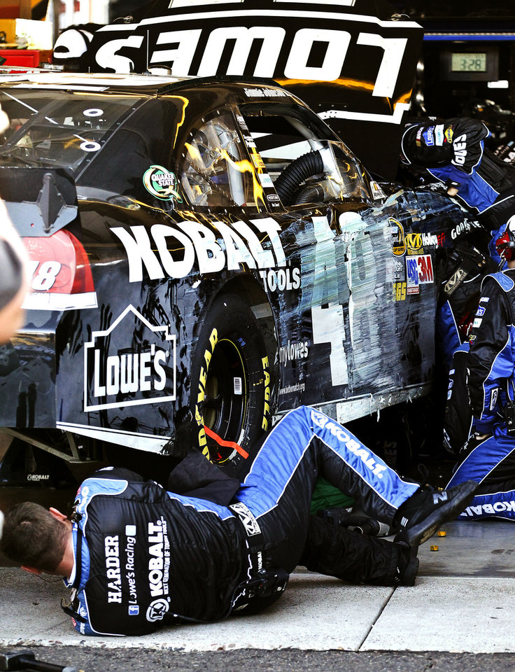Crew members work on Jimmie Johnson's (48) car in the garage after he crashed into the wall during the NASCAR Sprint Cup Series auto race at Phoenix International Raceway, Sunday, Nov. 11, 2012, in Avondale, Ariz. (AP Photo/Ross D. Franklin)