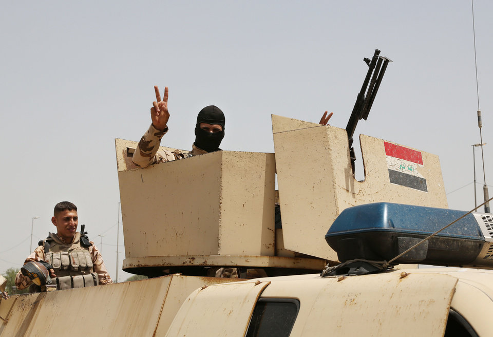 Photo - An Iraqi soldier flashes a V for victory sign while Iraqi men gather outside of the main army recruiting center to volunteer for military service in Baghdad, Iraq, Thursday, June. 12, 2014, after authorities urged Iraqis to help battle insurgents.  The al-Qaida-inspired group that led the charge in capturing two key Sunni-dominated cities in Iraq this week vowed on Thursday to march on to Baghdad, raising fears about the Shiite-led government's ability to slow the assault following the insurgents' lightning gains. (AP Photo/ Karim Kadim)
