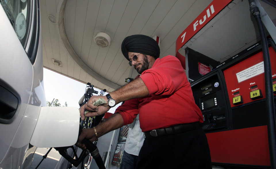 Photo -   Lukoil service station worker Harbhasan Singh pumps gas Wednesday, Sept. 12, 2012, in South Plainfield, N.J., for regular customer Tiffany Price who still bought gas in support, even though it was more than $8 a gallon. More than 50 Lukoil gas stations in New Jersey and Pennsylvania were jacking up prices to more than $8 a gallon Wednesday to protest what they say are unfair pricing practices by Lukoil North America that they say leave them at a competitive disadvantage. (AP Photo/Mel Evans)
