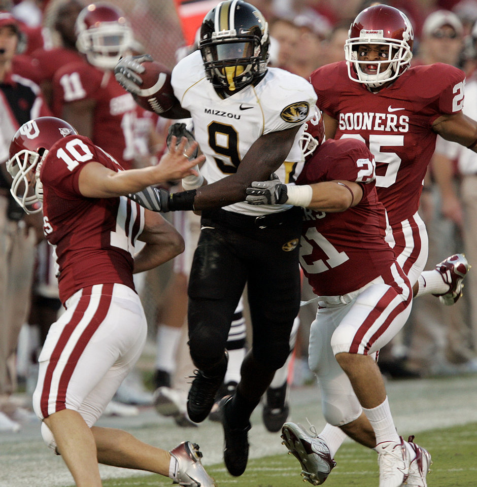 Photo - Oklahoma's Garrett Hartley (10) Jacob Gutierrez (21) and D.J. Wolfe (25) try to bring down Missouri's Jeremy Maclin (9) on a kick return during the first half of the college football game between  the University of Oklahoma Sooners (OU) and the University of Missouri Tigers (MU) at the Gaylord Family Oklahoma Memorial Stadium on Saturday, Oct. 13, 2007, in Norman, Okla. By STEVE GOOCH, The Oklahoman