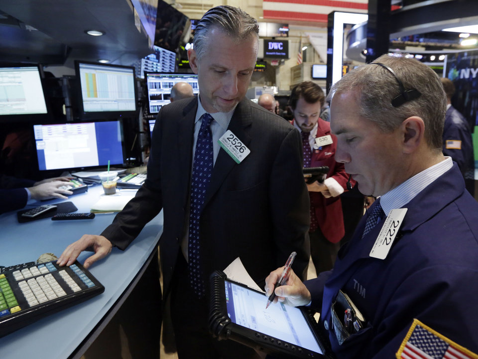 Photo -  Specialist Donald Himpele, left, and trader Timothy Nick work on the floor of the New York Stock Exchange.  AP Photo   Richard Drew -