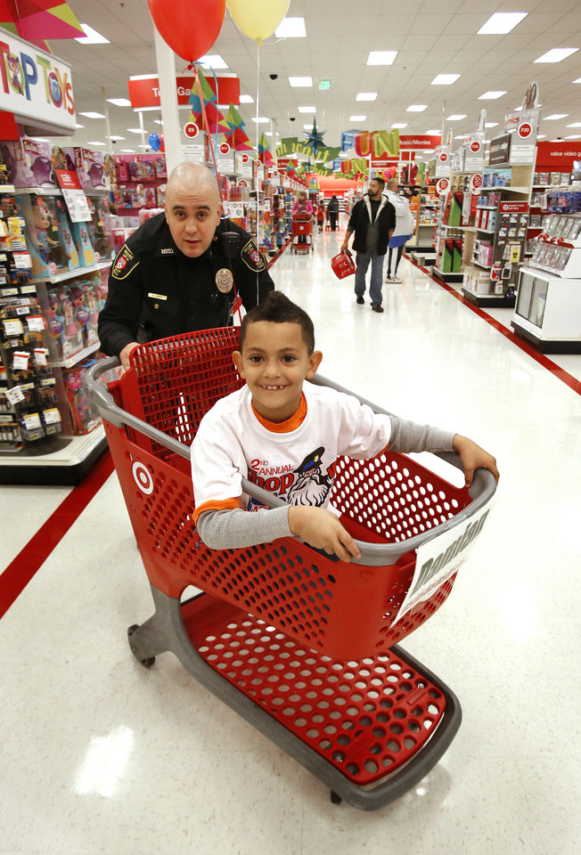 "Photo - Moore police officer Aaron Smith helps Damian  Johnson, 7, shop Saturday at Target during ""Shop With a Cop"" in Moore. Photos by Steve Sisney, The Oklahoman"