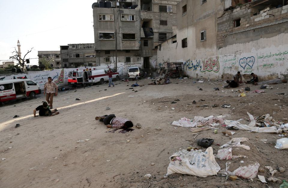 Photo - Palestinians lay on the ground following an Israeli Strike in Shijaiyah neighborhood, eastern Gaza City, Wednesday, July 30, 2014. (AP Photo/Adel Hana)