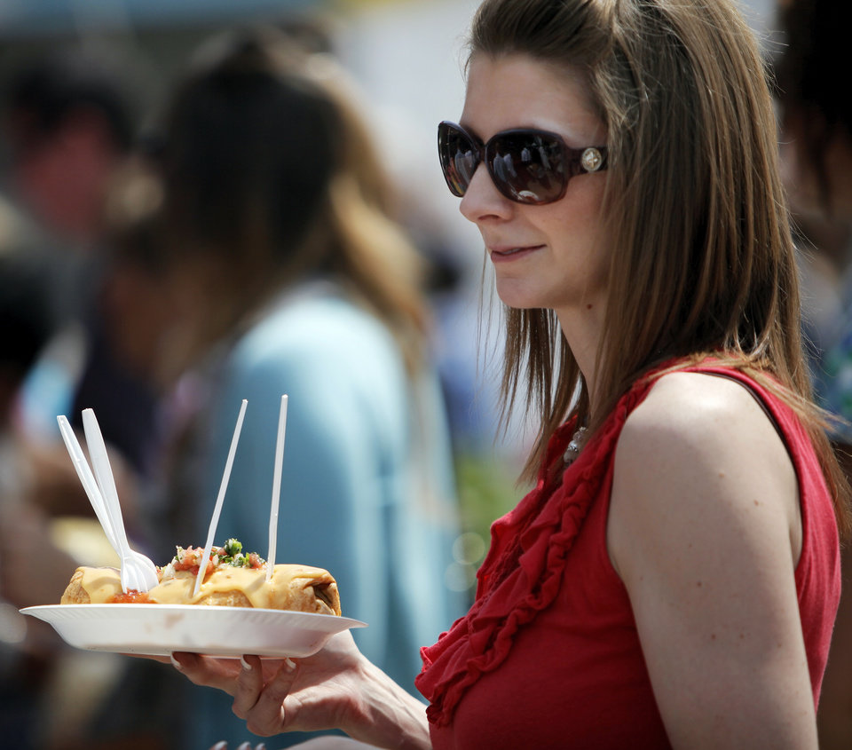 Amanda Templeton holds a Chipotle Beef Burrito from the Bodacious Burrito & Oklahoma Shakespeare in the Park booth on International Food Row during the Festival of the Arts in downtown Oklahoma City, Wednesday, April 25, 2012. Photo by Nate Billings, The Oklahoman